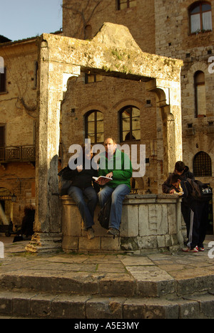 San Gimignano couple reading a guide book on the central well in  Tuscany Italy - Stock Photo