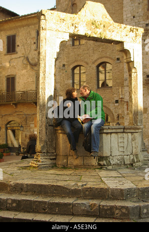 San Gimignano Romantic couple reading a guide book on the central well in  Tuscany Italy - Stock Photo