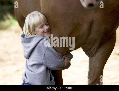 Small young girl hugs massive leg of Clydesdale Draft horse mare - Stock Photo