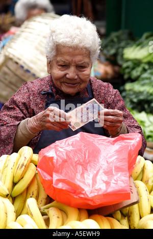 Hong Kong, Kowloon, Old woman selling bananas in the market checks a bill, China - Stock Photo