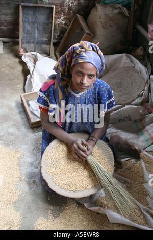Harar, Ethiopia, young woman threshing grain in a market - Stock Photo