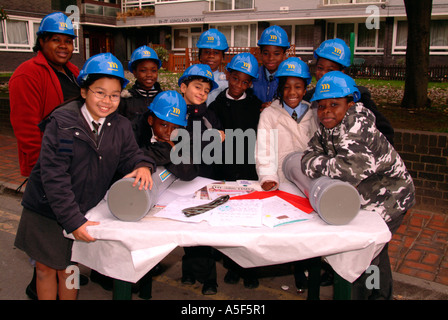 Schoolchildren posing with items to be put in a time capsule for burial on new housing development, Southwark, south - Stock Photo