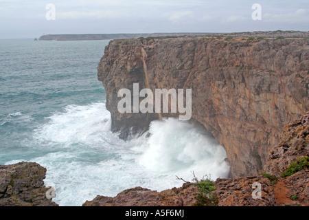 high waves through a cave at Sagres Fortaleza Algarve Portugal - Stock Photo