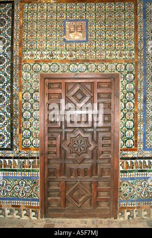 wooden door and tiled wall inside Casa de Pilatos Seville Andalucia Spain - Stock Photo