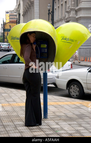 Woman talking on a public pay telephone in Sao Paulo Brazil - Stock Photo
