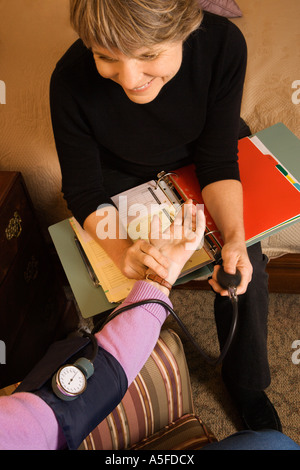 Elderly Caucasian woman at retirement community center receiving blood pressure test by nurse - Stock Photo