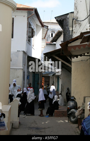 Zanzibar, Tanzania, Local schoolgirls playing in the narrow streets of Stonetown - Stock Photo