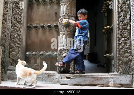 Small boy kicks at a cat in the narrow streets of Stonetown, Zanzibar, Tanzania - Stock Photo