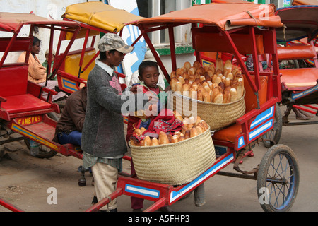Pousse pousse driver and boy unload bread in Ambalavao, Madagascar - Stock Photo
