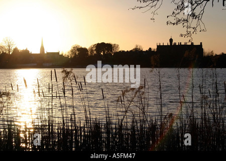 Sunset over the Park Lake, Lurgan with Brownlow House and the town in silhouette, County Armagh, Northern Ireland - Stock Photo