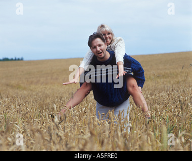 Situation in Field Girl Jumped on Boy s Backs - Stock Photo