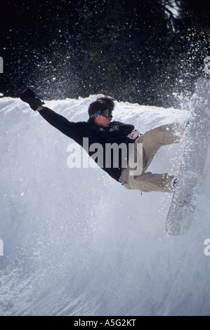 Snowboarder spraying snow in half pipe. - Stock Photo