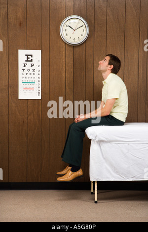 Caucasian mid adult male waiting on table in retro doctor s office - Stock Photo