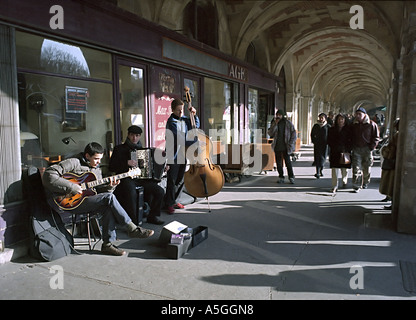 A band performs for tourists and passers by under the Place des Vosges arcades in Paris
