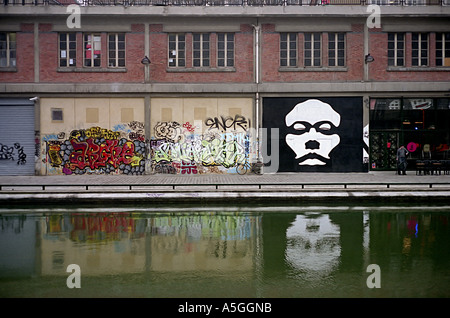 Mural paintings and graffiti adorn the wall of an industrial building on Canal Saint martin a waterway in the city - Stock Photo