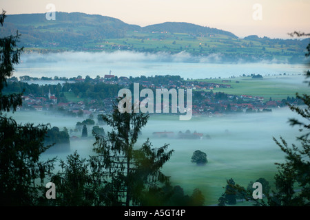 view from the mountain Tegelberg of Schwangau and Lake Forggen in Bavaria covered in morning fog - Stock Photo