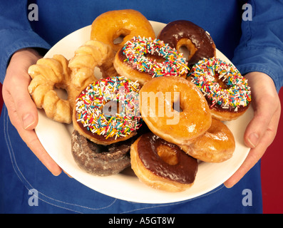 MAN HOLDING PLATE OF DOUGHNUTS - Stock Photo