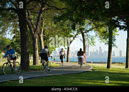 ILLINOIS Chicago Runners and bicyclists use paved path among trees along lakefront on summer morning skyline in - Stock Photo