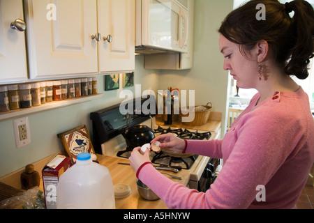 Detroit Michigan Mariel West 19 making scrambled eggs on the stove - Stock Photo