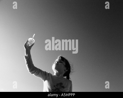little girl playing with soap bubbles in the park - Stock Photo