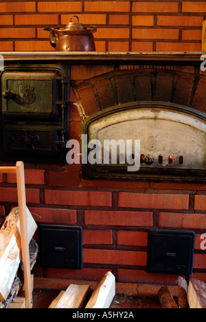PR old wood heated kitchen stove with baking oven made of stone - Stock Photo