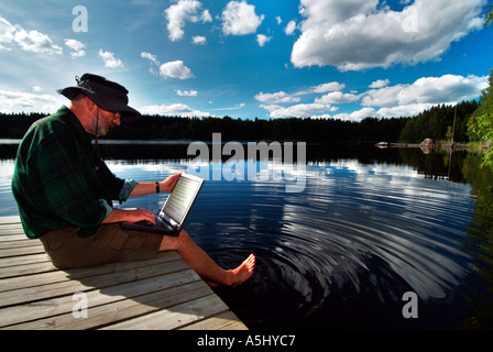 MR PR man sitting on a footbridge at a lake in Finland working with a notebook - Stock Photo