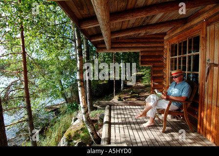 woman reading a book sitting on veranda of a sauna building at lakefront in Finland - Stock Photo