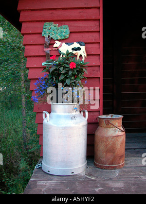 milk churn decorated with flowers - Stock Photo
