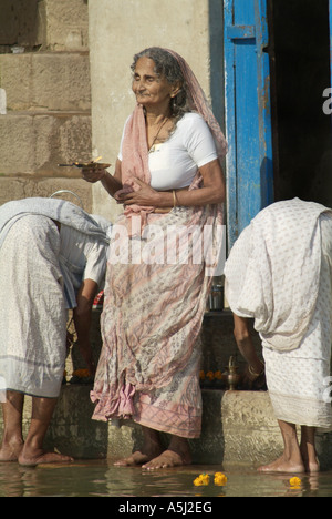Hindu woman praying on the banks of the Ganges River in Varanasi, India - Stock Photo