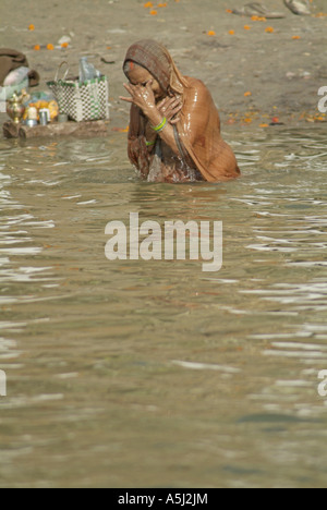 Woman bathing in the Ganges River in Varanasi, India - Stock Photo