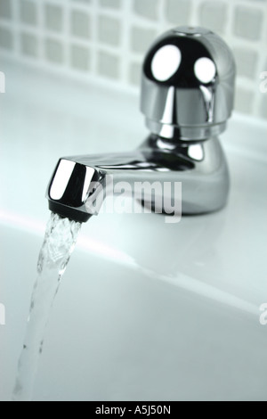 water running into sink from tap - Stock Photo