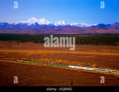 The Alaska Railroad southbound train passing through Summit in Denali National Park, with Mt McKinley in the background - Stock Photo