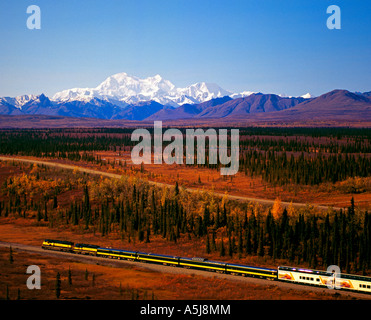 Alaska Railroad southbound train at the summit, with Mt McKinley and the Alaska Range in the background - Stock Photo