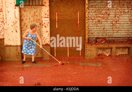 An old woman cleans up after the tomatina tomato festival in Buñol, Spain. Picture credit: Brian Hickey/Alamy - Stock Photo