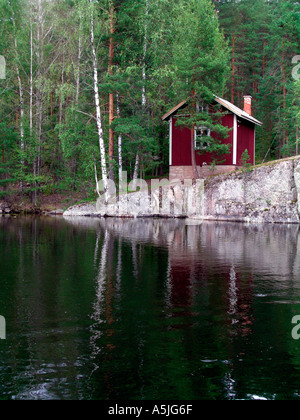 old little sauna cottage on rocks at lakefront in Finland - Stock Photo