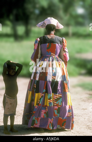 Herero Woman wearing a traditional patchwork dress and headdress with a child Botswana - Stock Photo