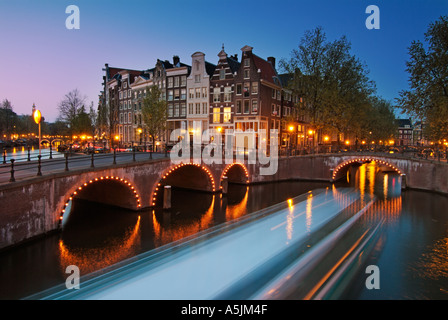 a cruise boat going under the Illuminated bridges of Keizersgracht and Leidsestraat Amsterdam Netherlands - Stock Photo