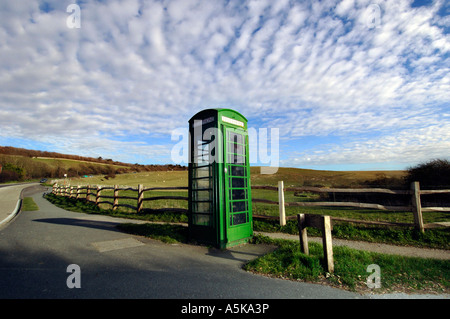 A British Telecom green K6 telephone box on a quiet county lane in Sussex - Stock Photo