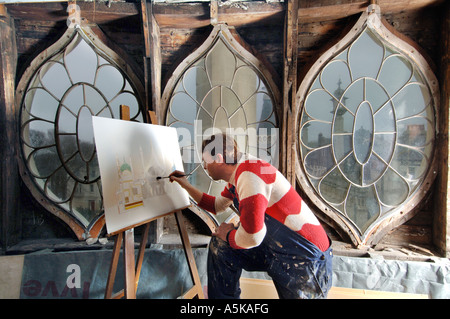Artist in residence at the Royal Pavilion Brighton painting the ornate regency gothic windows - Stock Photo