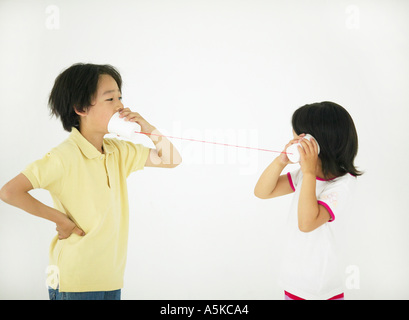 Young girl boy listening talking on toy telephone - Stock Photo