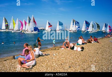 people on beach watching yacht racing Cowes Week Isle of Wight England UK - Stock Photo