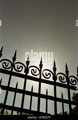wrought iron gate with sun breaking through  - Stock Photo
