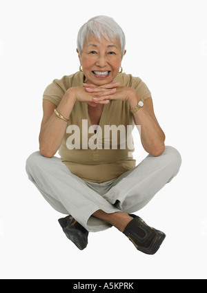 Studio shot of senior woman sitting cross legged - Stock Photo