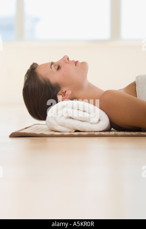 Woman laying on mat with rolled towel under neck - Stock Photo