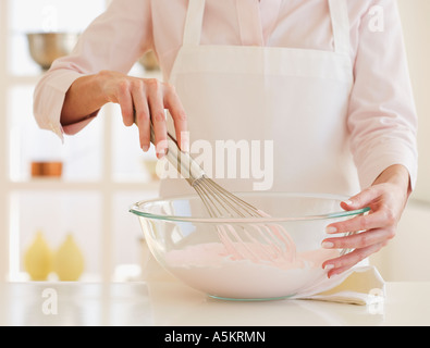 Woman wearing apron and mixing batter - Stock Photo