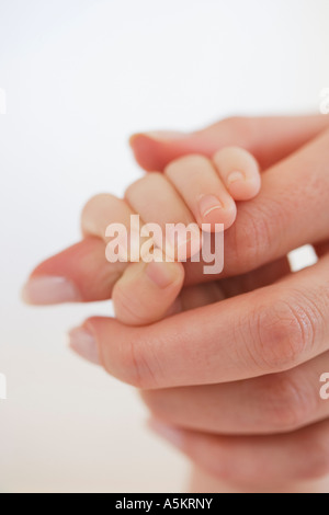 Close up of baby holding mother s hand - Stock Photo