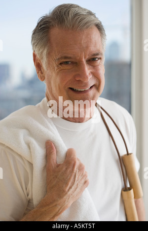 Portrait of senior man holding jump rope over shoulder