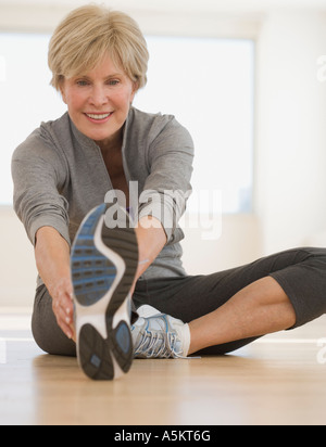 Senior woman stretching on floor - Stock Photo