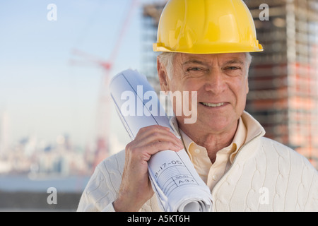Senior man wearing hard hat and holding blueprints - Stock Photo