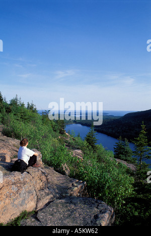 Hiker sitting on rock overlooking water - Stock Photo